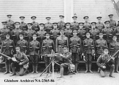 Group Photo – Photo:Machine gun section, 82nd Battalion, Canadian Expeditionary Force, Calgary, Alberta. L-R back row: W. de Mandey; F. Hills; F. Telford; H. Clowes; L. Allison; H. Hickey; W. Smitherun; F. Wells; M. Birchenough; S. Brown. (All others in the photograph are unidentified.) + Herbert Charles Hickey (marked with X in the back row), was born in 1893 and killed at Vimy Ridge in 1917. He is buried in Quatre-Vents Military Cemetery in Estree-Cauchie, Pas-de-Calais, France. He was born in Bristol and had worked for the CPR in Calgary. Glenbow Archives credit. Source: CVWM