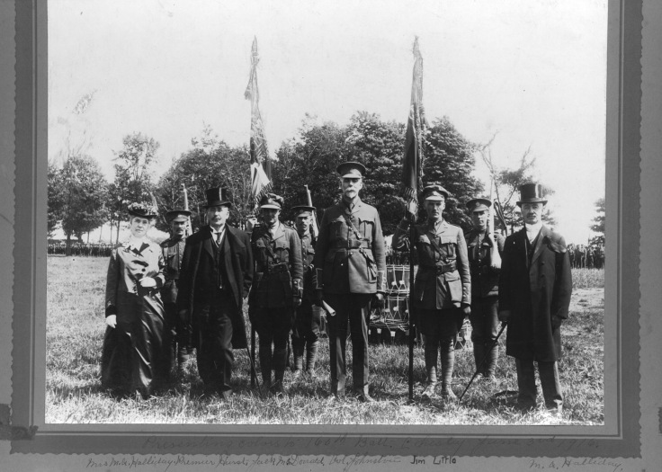 Photograph featuring Mr. and Mrs. Halliday, Premier Hearst, Jack McDonald, Col. Johnston, Capt. James Clow Little and M.A. Halliday at the presentation of colours to the 160th Battalion in Chesley on June 3, 1916. Source: Bruce County Museum Online Collections.